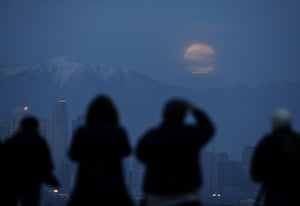 People watch the supermoon rise behind the downtown Los Angeles skyline, from Kenneth Hahn Park in Los Angeles