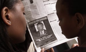 Readers look at a photograph of Rwandan Felicien Kabuga, who is wanted by the US, in a newspaper in Nairobi in June 2002.