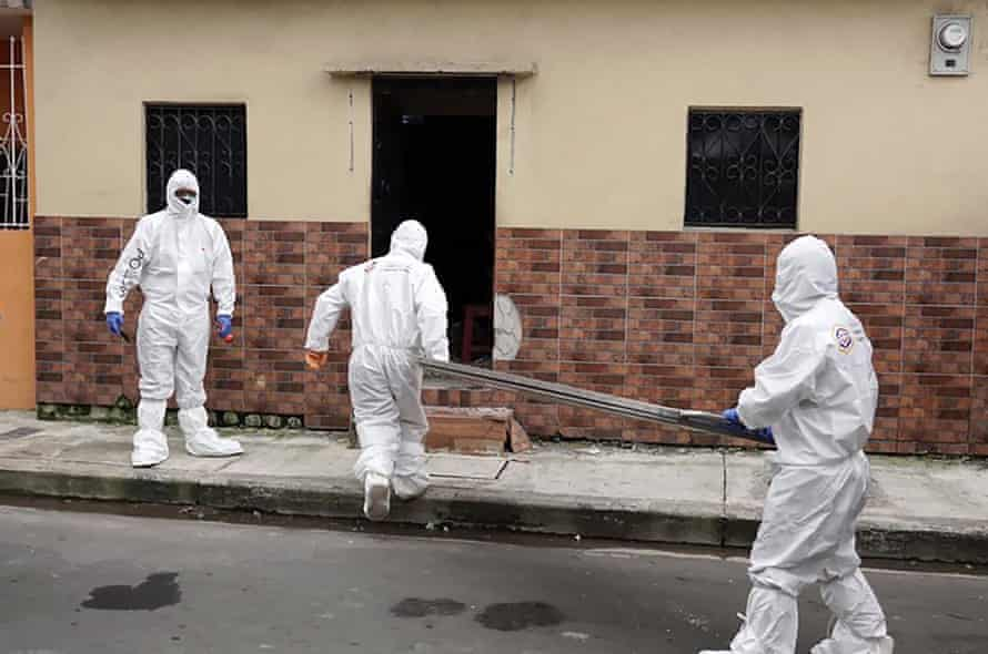 Police officers and medical personnel collect a body from a house