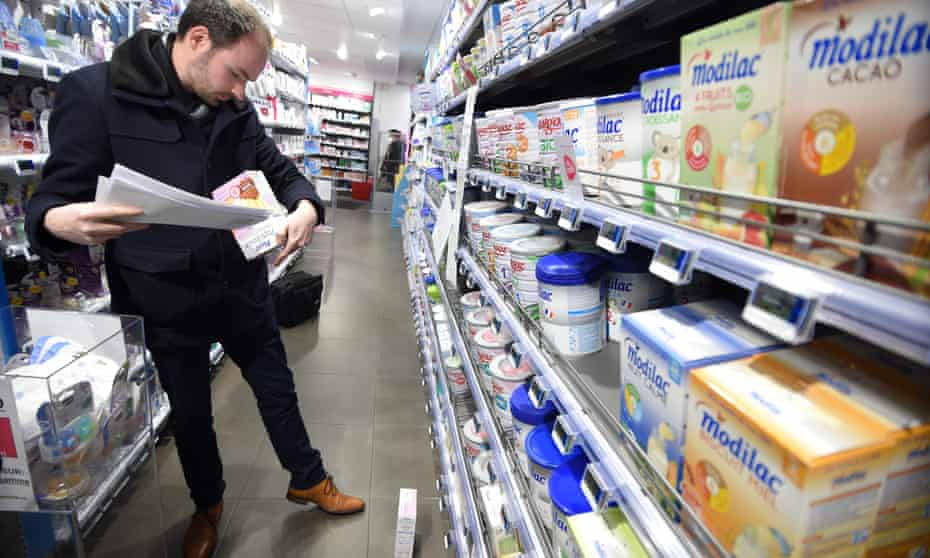 A French government official checks baby milk products in a pharmacy in Orleans