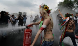 Women of Femen stage a topless protest in front of the Warsaw stadium in 2012.