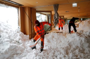 Workers shovel snow out of a restaurant after an avalanche at Santis-Schwaegalp mountain resort, in Switzerland