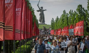 The 'Immortal Regiment' march up Mamayev Kurgan hill, a key location in the battle of Stalingrad, with the Motherland Calls statue in the background. Many carry portraits of their forefathers who took part in the battle.