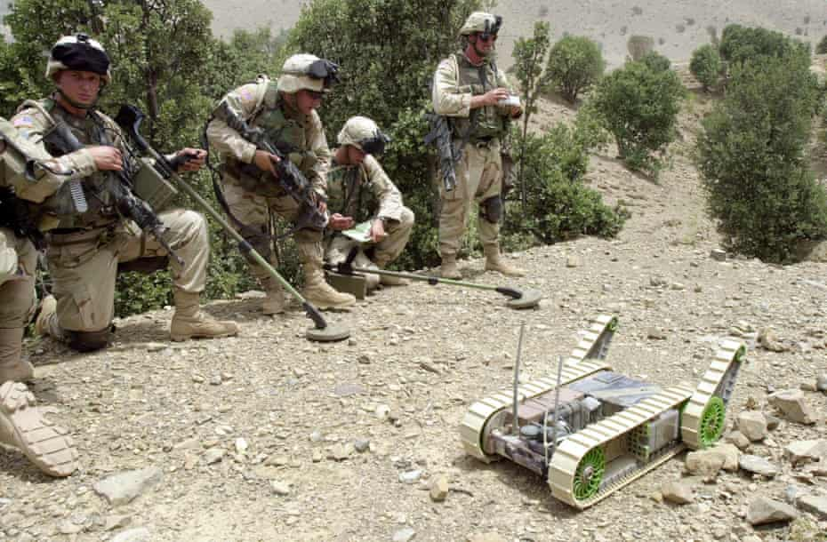US soldiers alongside a landmine detection robot in Afghanistan.