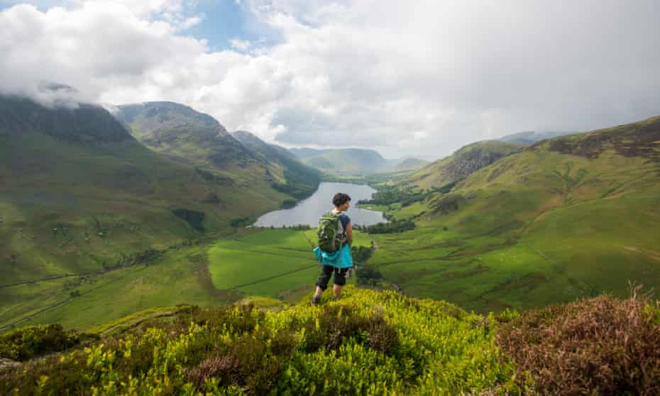 A woman looks out over Buttermere from the Fleetwith Pike in in The Lake District.Buttermere, Cumbria, The Lake District, England.