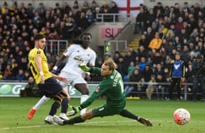 Gomis shoots past goalkeeper Slocombe to score Swansea's second.
