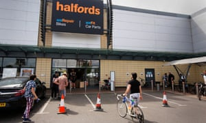 Shoppers queue outside a Halfords in Tottenham Hale, north London, in May.