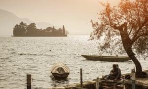 Couple sitting on the edge of Lake Iseo, Italy.