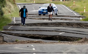 Local residents Chris and Viv Young look at damage caused by an earthquake along State Highway One near the town of Ward.
