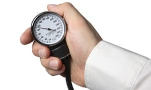 Hand holding a blood pressure gauge
