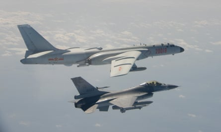 A Taiwanese F-16 fighter jet flies next to a Chinese H-6 bomber (top) in Taiwan airspace. China has sanctioned major US defence companies for selling weapons to Taipei.