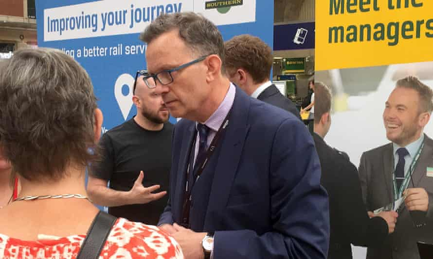 Charles Horton speaking to customers at Victoria station in London in July