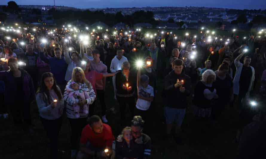 People hold up candles and mobile phone torches during a vigil in Keyham