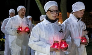 Staff of the Chernobyl nuclear plant hold candles as they visit a memorial, dedicated to firefighters and workers who died after the Chernobyl nuclear disaster.