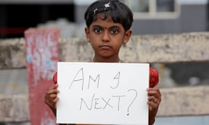 young girl holds a placard during a protest against the rape of an eight-year-old girl in Kathua, near Jammu, India