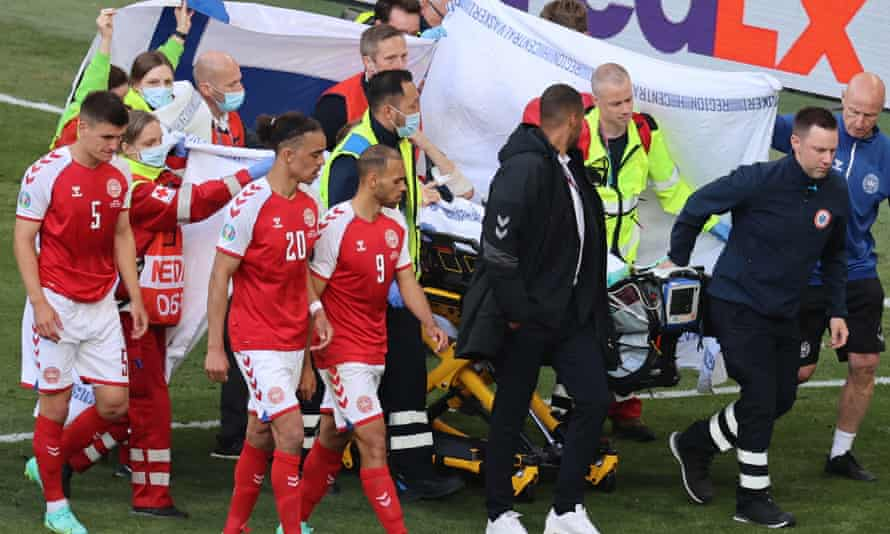 Christian Eriksen's teammates shield him from view as he is taken off the pitch by medical staff.