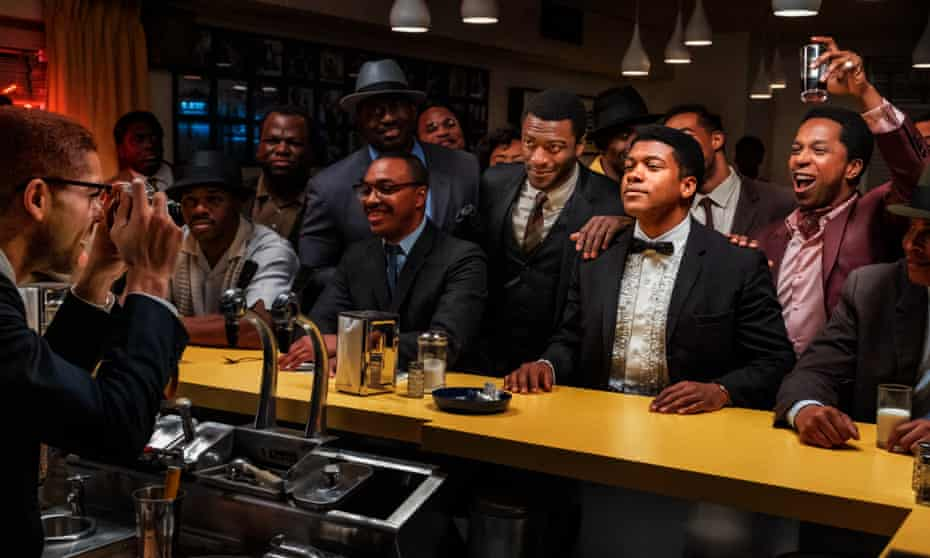 Kingsley Ben-Adir as Malcolm X, left, taking a photo of Aldis Hodge (standing, centre, in white shirt) as Jim Brown, Eli Goree (in tux) as Cassius Clay and Leslie Odom Jr (raising glass) as Sam Cooke in One Night in Miami.