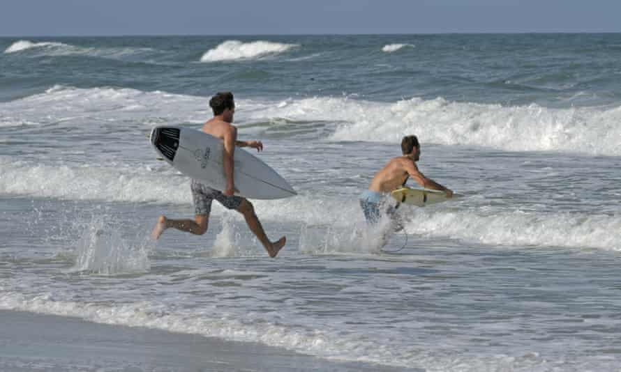 Surfers run into the waves in Jacksonville Beach.