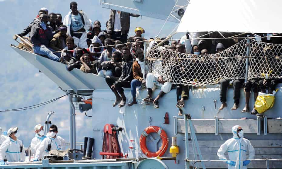 Refugees wait to disembark from the Italian Navy vessel Chimera in the harbor of Salerno, Italy.