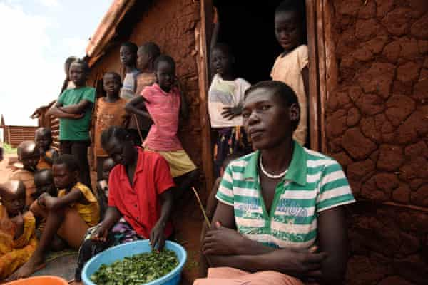 Monica Abau (right), 37, sits with her family outside their home in Kiryandongo refugee settlement