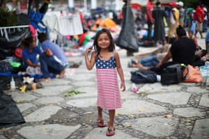 Chelsy Montserrat Maldonado, a four-year-old migrant girl from Honduras, part of a caravan of thousands from Central America en route to the United States, wears a U.S. flag themed dress as she stands in a makeshift camp as they take rest in Tapanatepec, Mexico