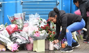A young woman adds flowers to tributes