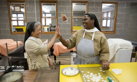 Sister Maria Eden, left, and Sister Thereza laugh as they make communion wafers at the Monastery of Saint Clare in Langhorne, Pennsylvania.