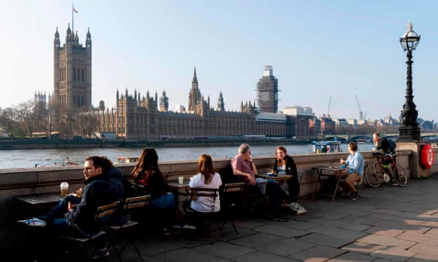People sitting by the River Thames opposite the Houses of Parliament.