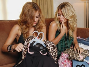 Mary-Kate and Ashley Olsen look over items from their fashion line.