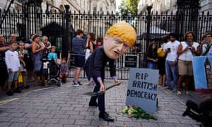 A protester depicting Boris Johnson burying democracy demonstrates outside the gates of Downing Street