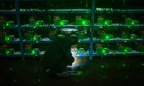 Bitcoin miner Huang inspects a malfunctioning mining machine during his night shift at the Bitcoin mine in Sichuan Province, China