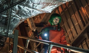A green-haired James Buckley as Nevi.
