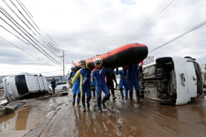 Rescue workers carry a rubber dinghy as they search a flooded area in Nagano prefecture.