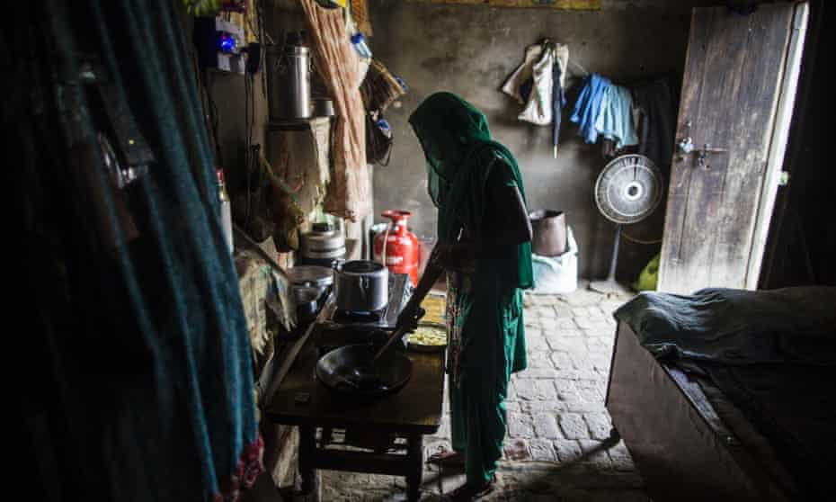 A woman cooks food on a gas-connected stove at her home in the village of Mangrauli in India's Uttar Pradesh state