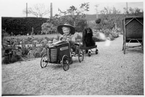 A young boy in his Cyclops Chevrolet pedal car – with his dog behind him in the wagon