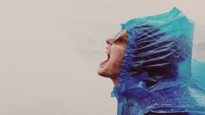 Close up of woman shouting into the spray, standing at the base of the American side of Niagara Falls.
