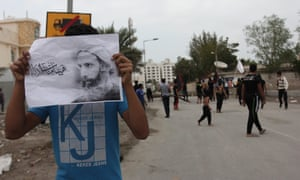 A Bahraini protester holds a picture of Nimr.