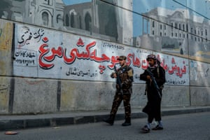 Taliban fighters patrol a road against the backdrop of a mural painted on a wall in Kabul on 26 September.
