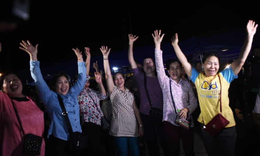Volunteers celebrate at a makeshift press centre in Mae Sai district on 10 July  2018, after the 12 boys and their football coach are rescued.