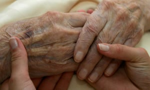A young carer holds the hands of an elderly woman