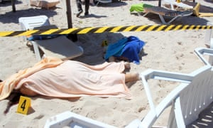 Bodies lie covered by their towels on the beach in Sousse.