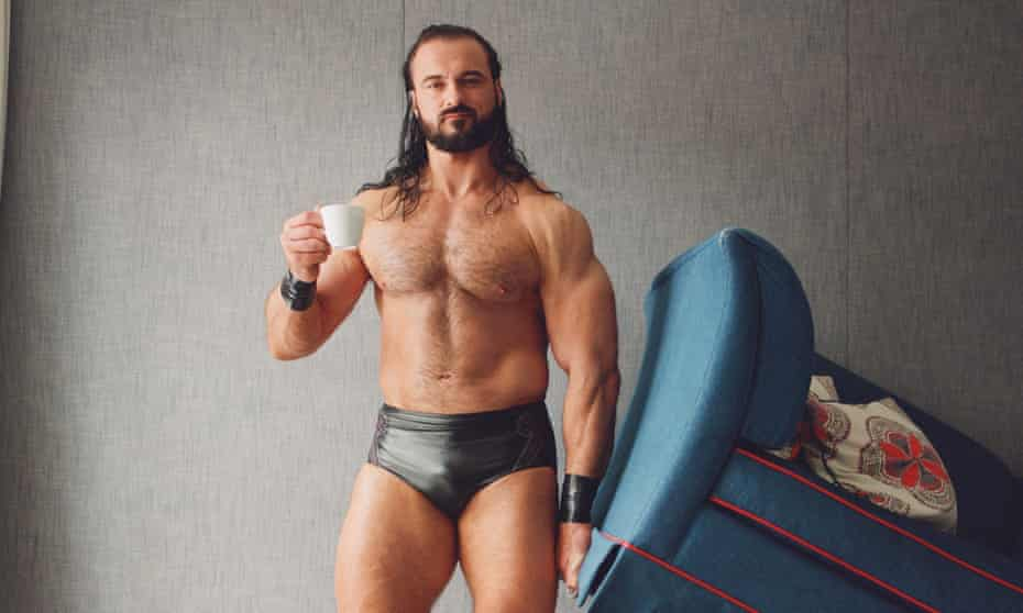 Drew McIntyre, dressed only in pewter-coloured underpants and matching wristbands, holding a cup of tea in one hand and lifting the end of the sofa up with the other