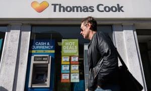 a man passes a Thomas Cook shop