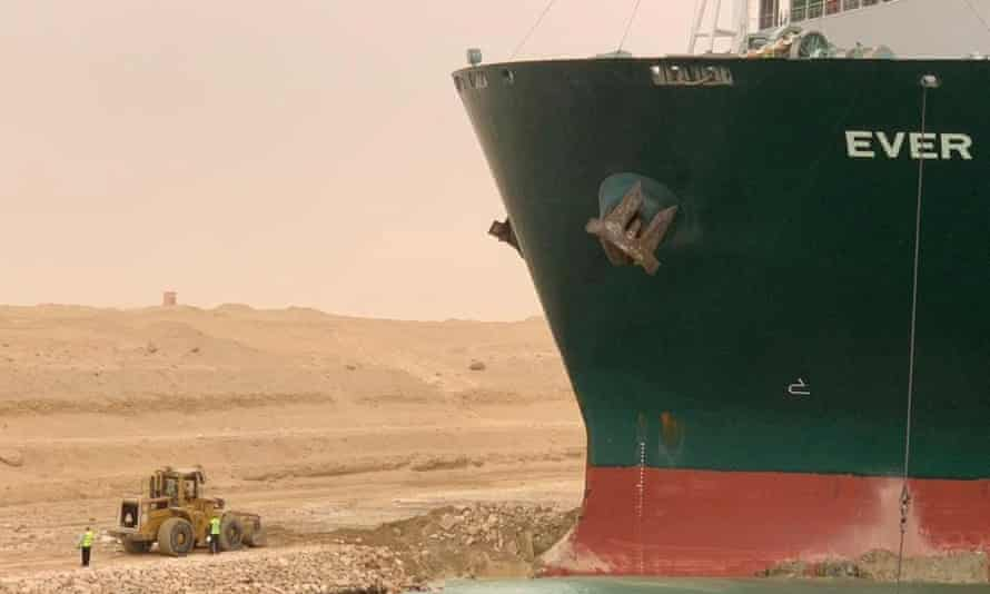Workers are seen next to the container ship which was hit by strong wind and ran aground in Suez Canal