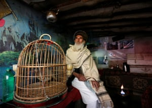 Mohammad Jan sits beside a partridge in a cage