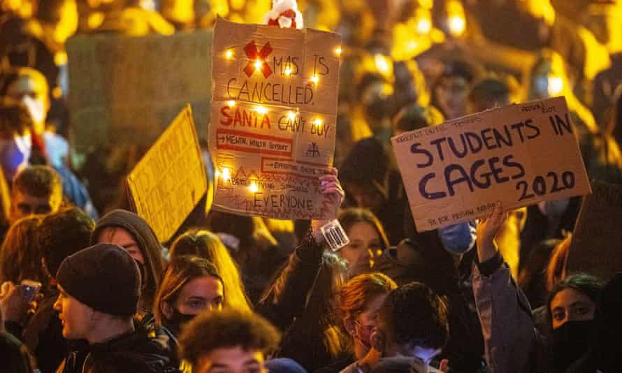 Students protest and march through the campus after tearing down fences at Manchester University.
