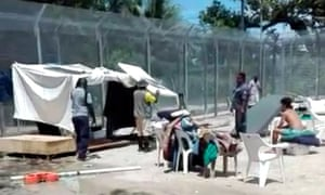 Papua New Guinean workers dismantle a makeshift water catchment tent at the Manus Island detention centre