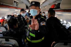 A police officer holds his hand up to the photographer as he orders Reuters journalists off a plane parked at Urumqi airport, Xinjiang