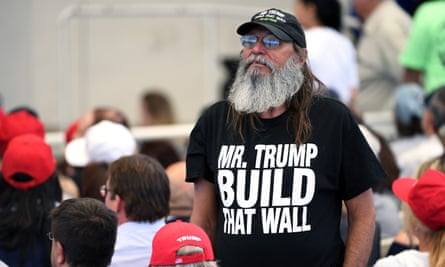 A Trump supporter in a T-shirt reading 'Mr Trump, Build That Wall'