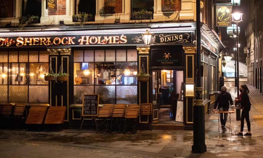 Staff pack away outdoor seating outside a pub in Westminster, London